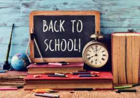 a chalkboard with the text back to school, some old books, an old clock, some pencil crayons and other old stationery, on a rustic wooden surface, against a blue wooden background
