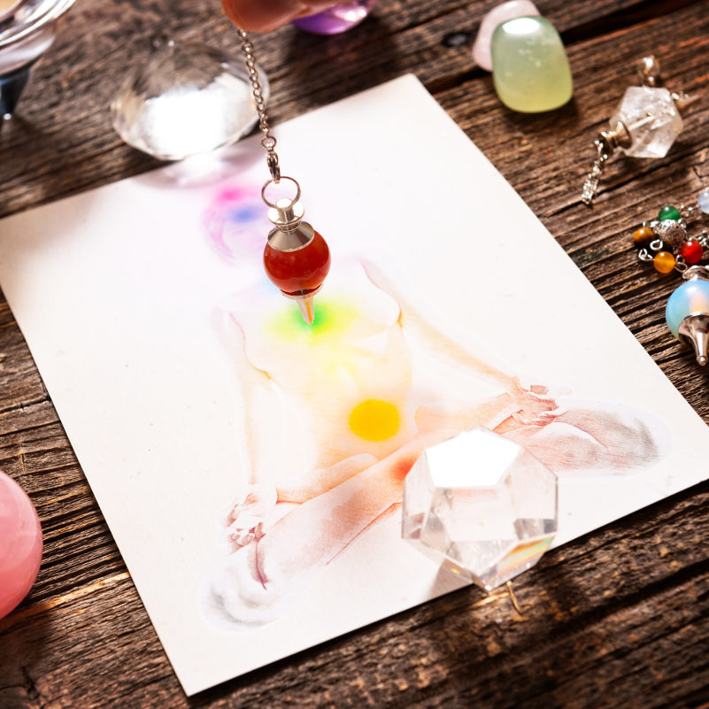 Chakras illustrated over human body with natural crystals and pendulum